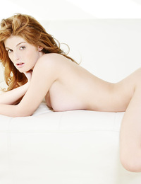 Faye,Deep Desire,Stunning redhead Faye looks you straight as she stretches out in the nude on a white couch.